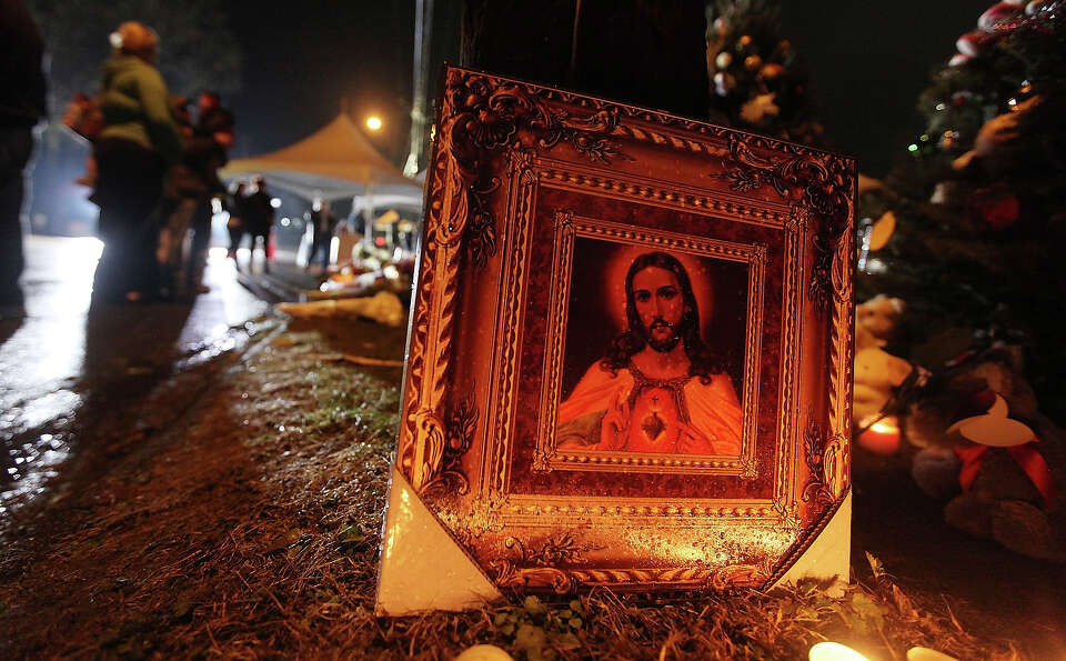 NEWTOWN, CT - DECEMBER 17: People gather near a Jesus painting at a memorial for victims of the mass