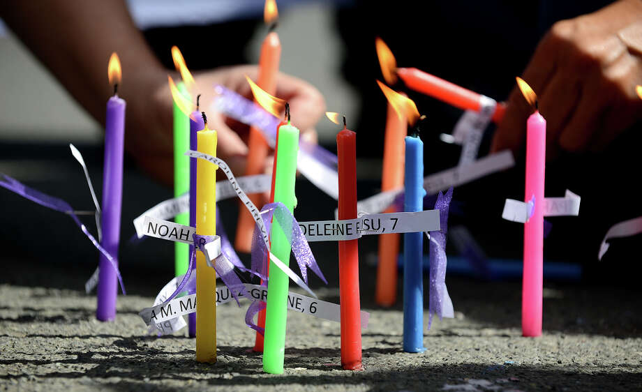 Members of human rights group, Volunteers Against Crime and Corruption (VACC), light candles with names of those killed during the shooting at Sandy Hook Elementary School in Newtown, Connecticut in the US, during a prayer vigil in front of the US Embassy in Manila on December 18, 2012.  Twenty children and six adults were reportedly killed by Adam Lanza, after he entered the school and opened fire. The massacre was the second-deadliest school shooting in the US after the 2007 Virginia Tech shooting. AFP PHOTO/NOEL CELIS Photo: NOEL CELIS, AFP/Getty Images / 2012 AFP