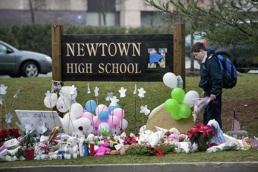 A student looks for a place to leave flowers at a makeshift memorial for the victims of the Sandy Ho