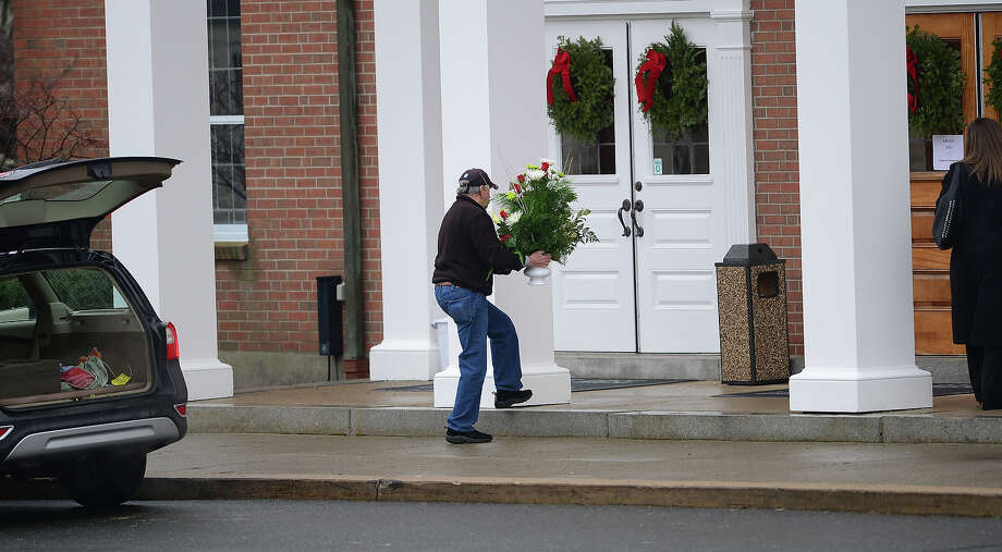 A man arrives with flowers for the funeral services of James Mattioli, 6  at Saint Rose of Lima Church on December 18, 2012 in Newtown, Connecticut.  Lawmakers are under mounting pressure to address the issue of gun laws in the aftermath of last week's school massacre in Newtown, Connecticut. AFP PHOTO/EMMANUEL DUNAND Photo: EMMANUEL DUNAND, AFP/Getty Images / 2012 AFP
