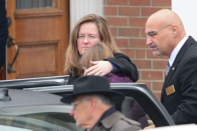 The casket of James Mattioli, 6 is carried into Saint Rose of Lima Church on December 18, 2012 in Newtown, Connecticut as his sister Anna and mother Cindy(C) arrive for the funeral.  Lawmakers are under mounting pressure to address the issue of gun laws in the aftermath of last week's school massacre in Newtown, Connecticut. AFP PHOTO/EMMANUEL DUNAND Photo: EMMANUEL DUNAND, AFP/Getty Images / 2012 AFP