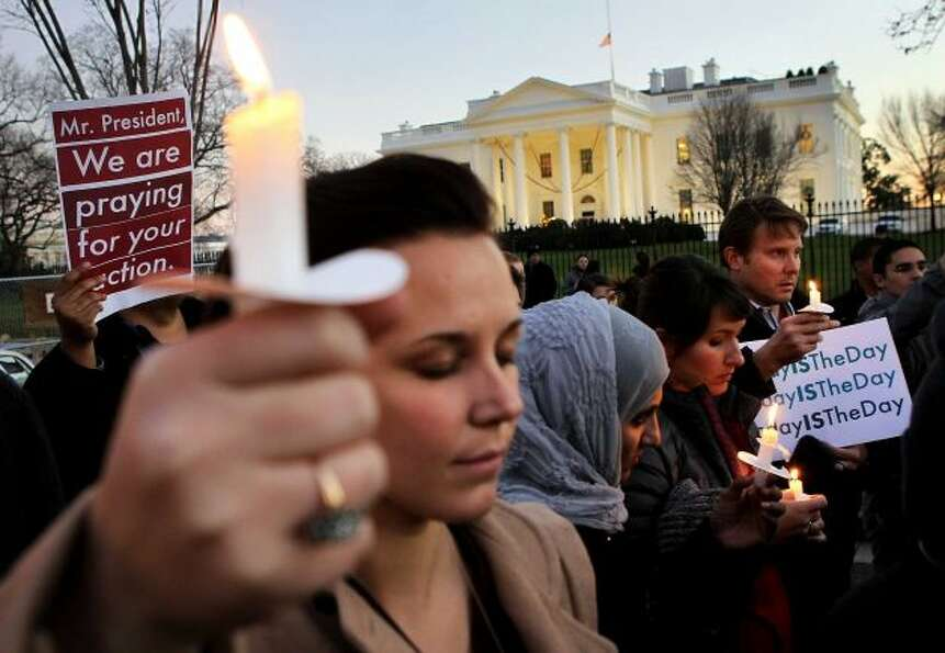 People gather outside the White House to participate in a candle light vigil to remember the victims