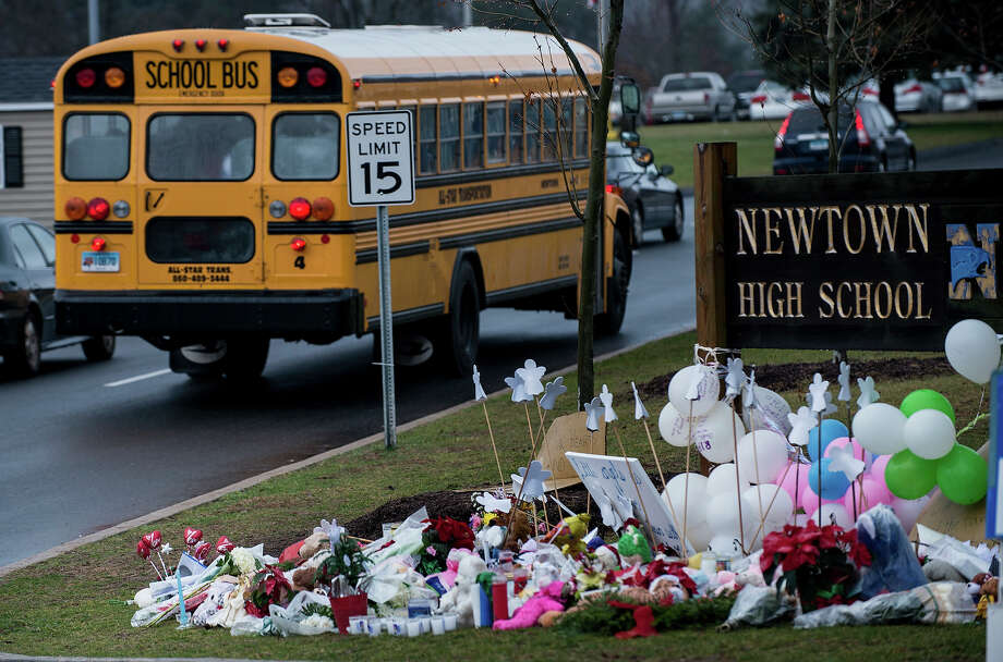 A school bus passes a makeshift memorial to the victims of the Sandy Hook Elementary School shooting as it takes students to Newtown High School December 18, 2012 in Newtown, Connecticut. Students in Newtown, excluding Sandy Hook Elementary School, return to school for the first time since last Friday's shooting at Sandy Hook which took the live of 20 students and 6 adults.  AFP PHOTO/Brendan SMIALOWSKI Photo: BRENDAN SMIALOWSKI, AFP/Getty Images / 2012 AFP