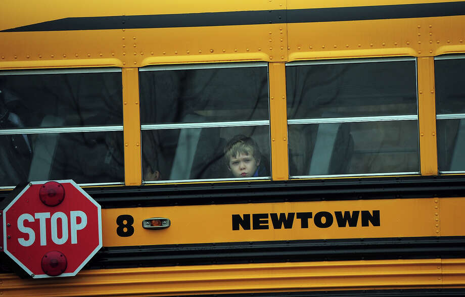 A child looks out of a bus window as it passes by Saint Rose of Lima Church where the funeral of James Mattioli, 6 is taking place on December 18, 2012 in Newtown, Connecticut.  Lawmakers are under mounting pressure to address the issue of gun laws in the aftermath of last week's school massacre in Newtown, Connecticut. AFP PHOTO/EMMANUEL DUNAND Photo: EMMANUEL DUNAND, AFP/Getty Images / 2012 AFP