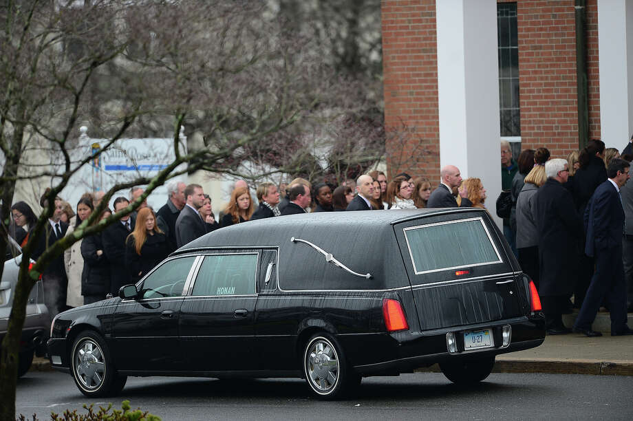 The casket of Jessica Rekos, 6 arrives at  Saint Rose of Lima Church as mourners gather on December 18, 2012 in Newtown, Connecticut for her funeral. Most children in Newtown returned to classes Tuesday for the first time since last week's massacre, but survivors of the shooting stayed at home and their school remained a crime scene. In a thin drizzle, yellow school buses once again rolled through the Connecticut town, where some 5,400 children are enrolled. AFP PHOTO/EMMANUEL DUNAND Photo: EMMANUEL DUNAND, AFP/Getty Images / 2012 AFP