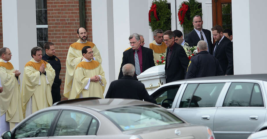 The casket of James Mattioli, 6 leaves Saint Rose of Lima Church as mourners gather on December 18, 2012 in Newtown, Connecticut after his funeral. Most children in Newtown returned to classes Tuesday for the first time since last week's massacre, but survivors of the shooting stayed at home and their school remained a crime scene. In a thin drizzle, yellow school buses once again rolled through the Connecticut town, where some 5,400 children are enrolled. AFP PHOTO/EMMANUEL DUNAND Photo: EMMANUEL DUNAND, AFP/Getty Images / 2012 AFP
