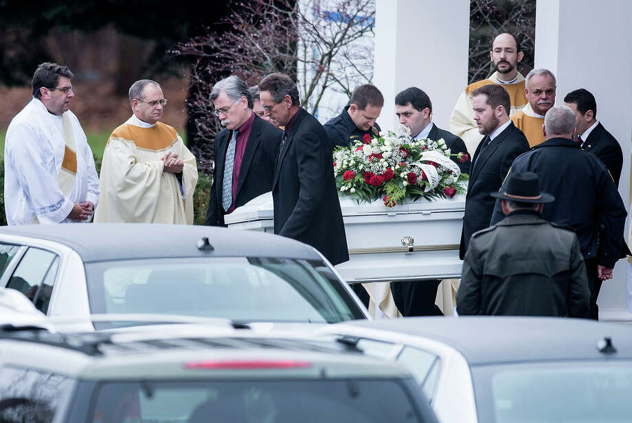 A casket with the body of James Mattioli is carried out of St. Rose of Lima Roman Catholic Church after a funeral Mass on December 18, 2012 in Newtown, Connecticut. Mattioli, age 6, is one of the victims from last Friday's shooting at Sandy Hook Elementary School which took the lives of 20 students and 6 adults.  AFP PHOTO/Brendan SMIALOWSKI Photo: BRENDAN SMIALOWSKI, AFP/Getty Images / 2012 AFP