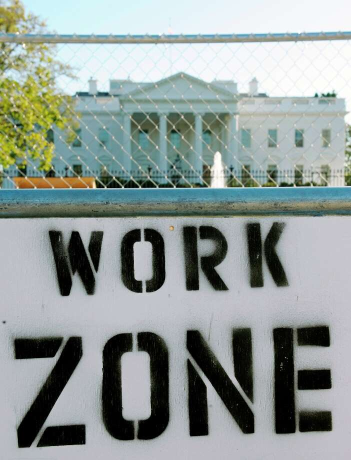 A sign on the security fence surrounding the construction area where workers are building the Presidential Inauguration reviewing stand in front of the White House in Washington, Thursday, Nov. 8, 2012. (Cliff Owen  / AP Photo) Photo: Cliff Owen, Associated Press / FR170079 AP