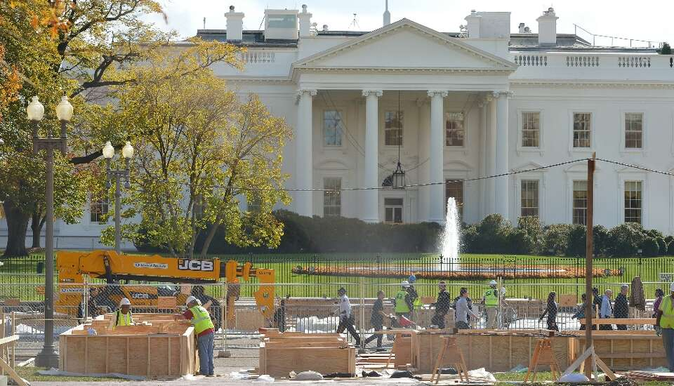 Workers are seen infront of the White House during preparation of a review stand for the presidentia
