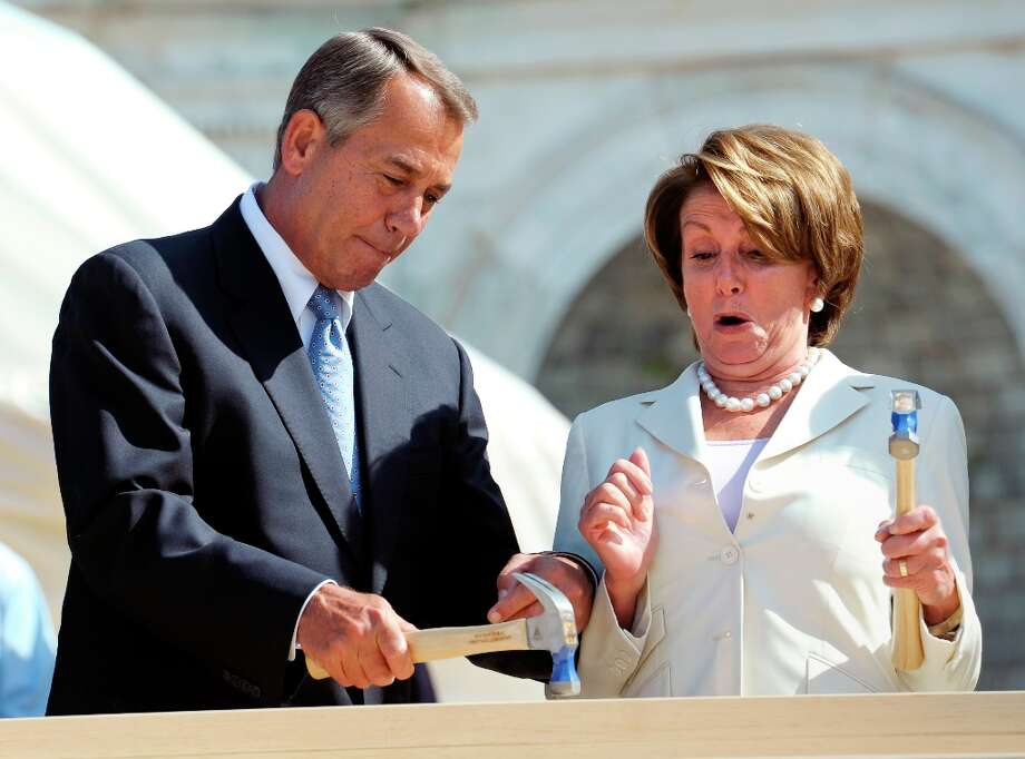 Speaker of the House John  Boehner, R-Ohio, left, finishes hammering a nail into a plank with House Democratic Leader Nancy Pelosi, D-Calif., right, nail into a plank during the First Nail Ceremony for the official launch of construction of the Inaugural platform where the President of the United States will take the oath of office on the West Front of the U.S. Capitol in Washington, Thursday, Sept. 20, 2012. (AP Photo/Cliff Owen) (Cliff Owen / AP Photo) Photo: Cliff Owen, Associated Press / FR170079 AP