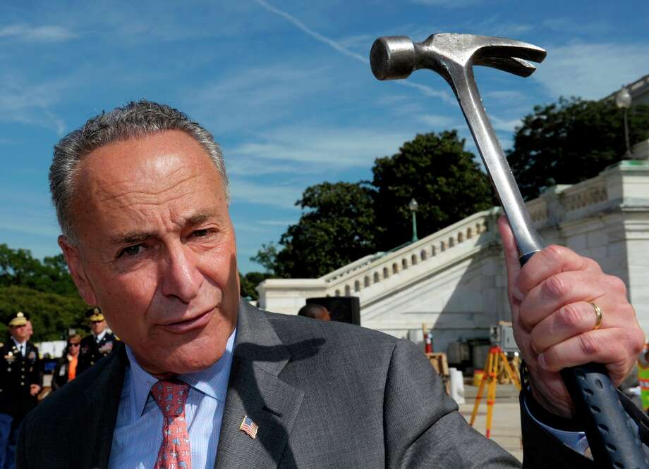 Senator Charles E. Schumer, D-N.Y., displays the hammer he used during the First Nail Ceremony for the official launch of construction of the Inaugural platform where the President of the United States will take the oath of office on the West Front of the U.S. Capitol in Washington, Thursday, Sept. 20, 2012. Schumer said the hammer belongs to a Connecticut carpenter who is working on the new One World Trade Center building.  (Cliff Owen / AP Photo) Photo: Cliff Owen, Associated Press / FR170079 AP