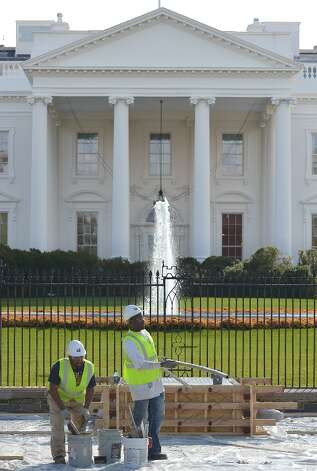 Workers are seen in front of the White House on Pennsylvania Avenue during preparation of a review stand for the presidential inauguration on November 12, 2012. The Presidential Inauguration will take place on January 21, 2013. Photo: MANDEL NGAN, AFP/Getty Images / AFP
