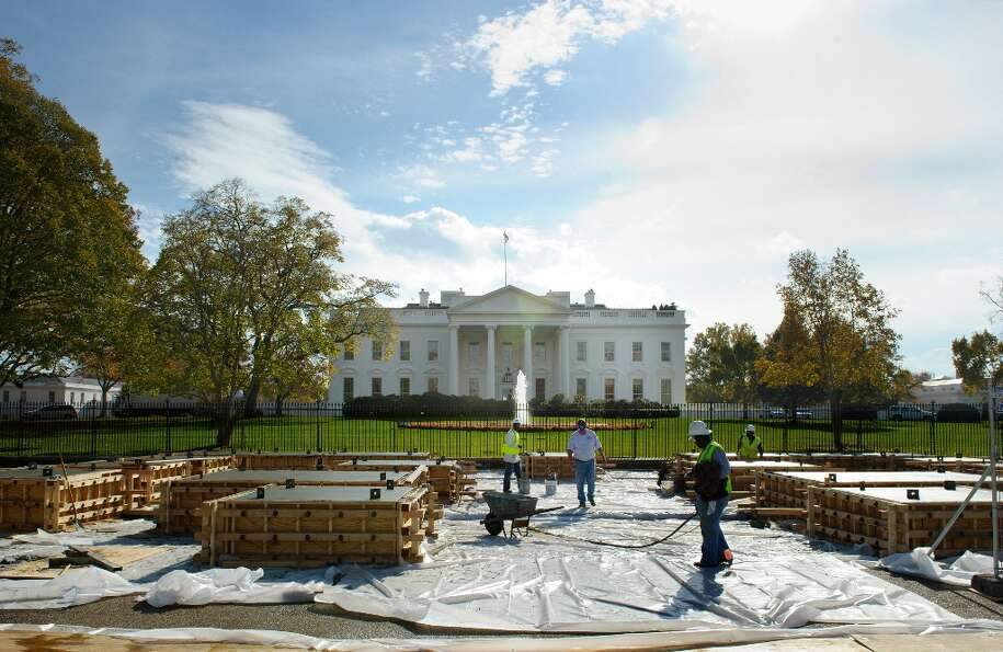 Workers are seen in front of the White House on Pennsylvania Avenue during preparation of a review s