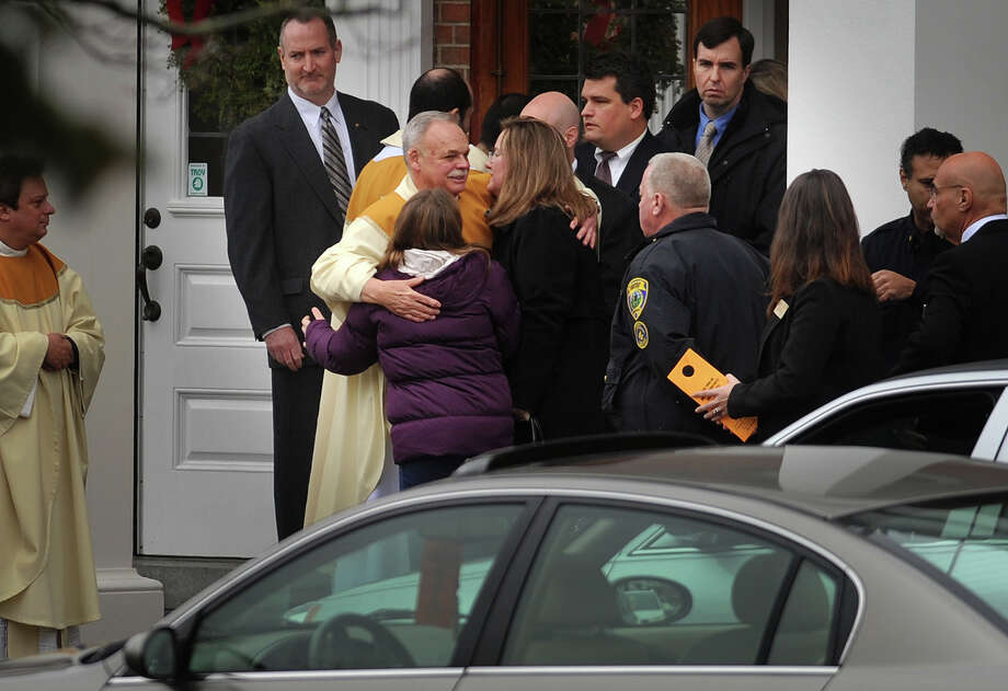 Cindy Mattioli and Anna Mattioli, mother and sister of James Mattioli, one of the students killed in the Sandy Hook Elementary School shooting, embrace clergy following James Mattioli's funeral at St. Rose of Lima Catholic Church in Newtown on Tuesday, December 18, 2012. Photo: Brian A. Pounds / Connecticut Post