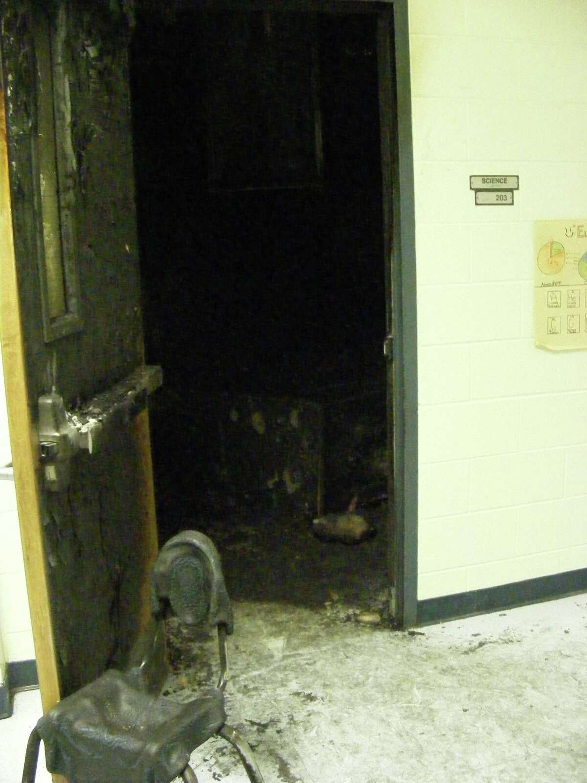 A melted chair props open a charred door to a blackened classroom at Kirby Middle School. A Dec. 12 fire torched the classroom.