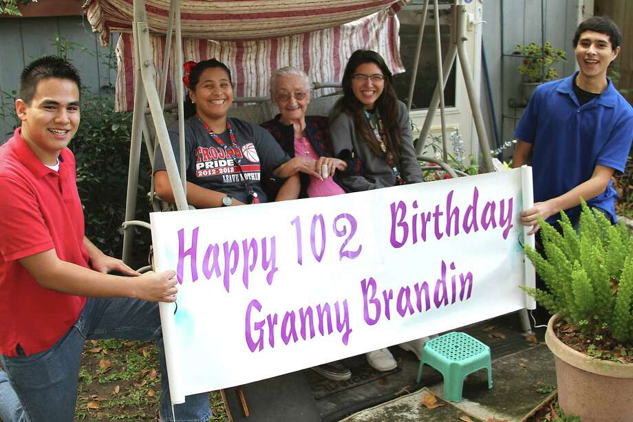 Elodia Brandin, who turned 102 last month, shares an afternoon in her swing with her birthday visitors from South Houston High School. Holding the birthday banner are J.C. Longoria and Alvaro Gonzalez. Sitting with the birthday girl are sisters Gabby and Sophia Villarreal.  Elodia Brandin, who turned 102 last month, shares an afternoon in her swing with her birthday visitors from South Houston High School. Holding the birthday banner are J.C. Longoria and Alvaro Gonzalez. Sitting with the birthday girl are sisters Gabby and Sophia Villarreal.