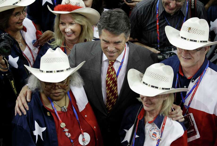 Texas Governor Rick Perry poses with delegates during the Republican National Convention in Tampa, Fla., on Tuesday, Aug. 28, 2012. Photo: Charlie Neibergall, Associated Press / AP