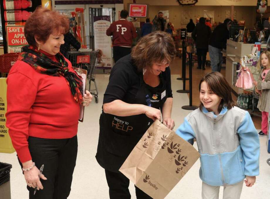 Mae Cimmino,  left, of Sandy Hook, CT, looks on as, Karen Bertanza, center, of Shelton, CT, holds a bag of raffle tickets as, Angelina Ruggiero, right, 12, of Monroe, CT, draws a winning ticket during a fund raising event for the family of Becky Lohrenz, at Stop & Shop, in Newtown, CT, on Saturday, Dec. 19, 2009.  Lohrenz, an employee of Stop & Shop, and the mother of two children, passed away earlier this year. Photo: Jay Weir / The News-Times