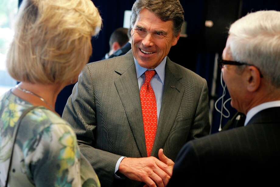 Texas Gov. Rick Perry speaks with outgoing Angelo State University president Joseph Rallo and his wife Barbara after attending a press conference, Wednesday, Oct. 3, 2012, in San Angelo, Texas, detailing ASU's new $10,000 bachelor's degree plan. Nine other universities around the state have also adopted the more affordable plan stemming from a challenge from the governor's office in February 2011. (AP Photo/San Angelo Standard-Times, Patrick Dove) Photo: Patrick Dove, Associated Press / San Angelo Standard-Times