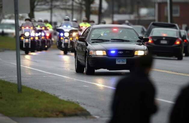 NEWTOWN, CT - DECEMBER 18:  Police drive ahead of a hearse carrying the body of shooting victim James Mattioli, 6, arrives for his funeral at the St. Rose of Lima Catholic church on December 18, 2012 in Newtown, Connecticut. Funeral services were held at the church for both James Mattioli and Jessica Rekos, 6, Tuesday, four days after 20 children and six adults were killed at Sandy Hook Elementary School.  (Photo by John Moore/Getty Images) Photo: John Moore, Getty Images / 2012 Getty Images