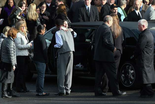 NEWTOWN, CT - DECEMBER 18:  Mourners embrace after a funeral for Jessica Rekos, 6, at the St. Rose of Lima Catholic church on December 18, 2012 in Newtown, Connecticut. Funeral services were held at the church for both Jessica Rekos and James Mattioli, 6, Tuesday, four days after 20 children and six adults were killed at Sandy Hook Elementary School.  (Photo by John Moore/Getty Images) Photo: John Moore, Getty Images / 2012 Getty Images