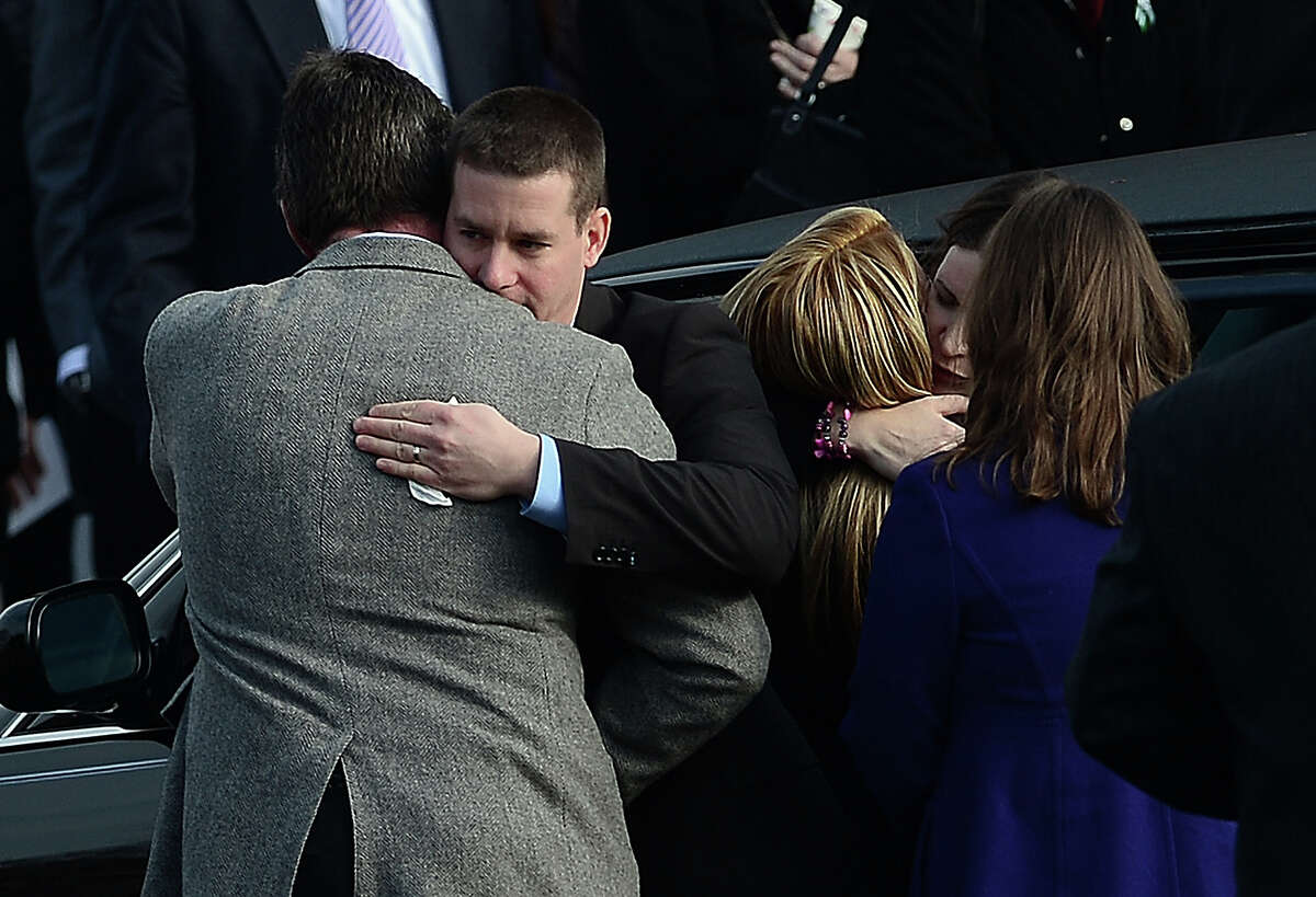 Richard (2ndL) and Krista (2ndR) Rekos, the parents of Jessica Rekos, 6, one of the 20 children killed in an elementary school shooting, are comforted after a funeral service at Saint Rose of Lima Church on December 18, 2012 in Newtown, Connecticut. Most children in Newtown returned to classes for the first time since last week's massacre, but survivors of the shooting stayed at home and their school remained a crime scene. In a thin drizzle, yellow school buses once again rolled through the Connecticut town, where some 5,400 children are enrolled. AFP PHOTO/EMMANUEL DUNAND