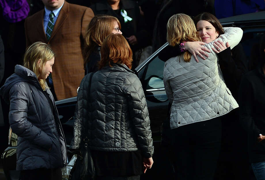 Krista (R) Rekos, the mother of Jessica Rekos, 6, one of the 20 children killed in an elementary school shooting, is comforted after a funeral service at Saint Rose of Lima Church on December 18, 2012 in Newtown, Connecticut. Most children in Newtown returned to classes for the first time since last week's massacre, but survivors of the shooting stayed at home and their school remained a crime scene. In a thin drizzle, yellow school buses once again rolled through the Connecticut town, where some 5,400 children are enrolled. AFP PHOTO/EMMANUEL DUNAND Photo: EMMANUEL DUNAND, AFP/Getty Images / 2012 AFP