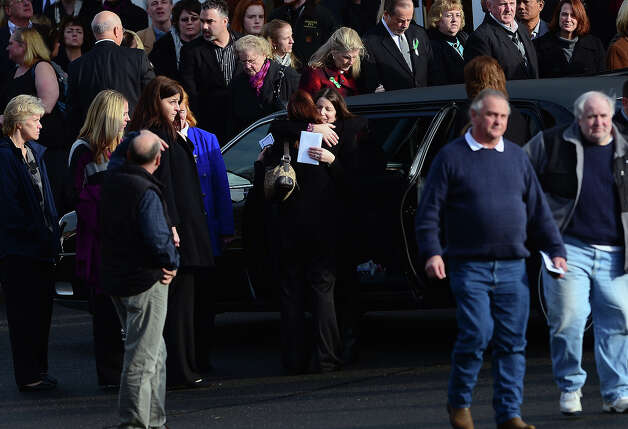 Krista Rekos(center R), the mother of Jessica Rekos, 6, one of the 20 children killed in an elementary school shooting, is comforted after a funeral service at Saint Rose of Lima Church on December 18, 2012 in Newtown, Connecticut. Most children in Newtown returned to classes for the first time since last week's massacre, but survivors of the shooting stayed at home and their school remained a crime scene. In a thin drizzle, yellow school buses once again rolled through the Connecticut town, where some 5,400 children are enrolled. AFP PHOTO/EMMANUEL DUNAND Photo: EMMANUEL DUNAND, AFP/Getty Images / 2012 AFP