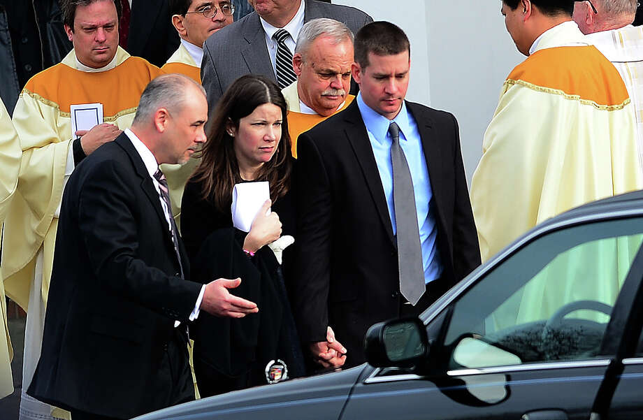 Richard (R) and Krista Rekos, the parents of Jessica Rekos, 6, one of the 20 children killed in an elementary school shooting, leave after a funeral service at Saint Rose of Lima Church on December 18, 2012 in Newtown, Connecticut. Most children in Newtown returned to classes for the first time since last week's massacre, but survivors of the shooting stayed at home and their school remained a crime scene. In a thin drizzle, yellow school buses once again rolled through the Connecticut town, where some 5,400 children are enrolled.    AFP PHOTO/EMMANUEL DUNAND Photo: EMMANUEL DUNAND, AFP/Getty Images / 2012 AFP