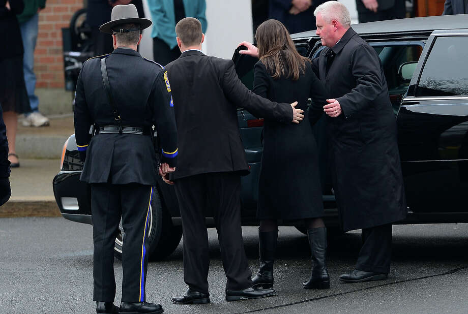 Richard(L) and Krista Rekos, the parents of Jessica Rekos, 6, one of the 20 children killed in an elementary school shooting, arrive for a funeral service at Saint Rose of Lima Church on December 18, 2012 in Newtown, Connecticut. Most children in Newtown returned to classes for the first time since last week's massacre, but survivors of the shooting stayed at home and their school remained a crime scene. In a thin drizzle, yellow school buses once again rolled through the Connecticut town, where some 5,400 children are enrolled. AFP PHOTO/EMMANUEL DUNAND Photo: EMMANUEL DUNAND, AFP/Getty Images / 2012 AFP