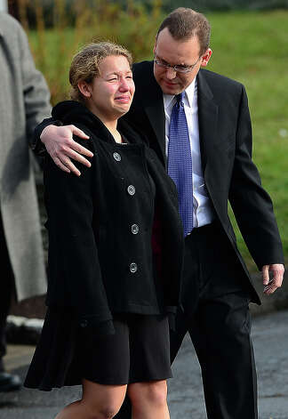 Mourners leave the funeral service of Jessica Rekos, 6, one of the victim of an elementary school shooting, at Saint Rose of Lima Church on December 18, 2012 in Newtown, Connecticut. Most children in Newtown returned to classes for the first time since last week's massacre, but survivors of the shooting stayed at home and their school remained a crime scene. In a thin drizzle, yellow school buses once again rolled through the Connecticut town, where some 5,400 children are enrolled. AFP PHOTO/EMMANUEL DUNAND Photo: EMMANUEL DUNAND, AFP/Getty Images / 2012 AFP