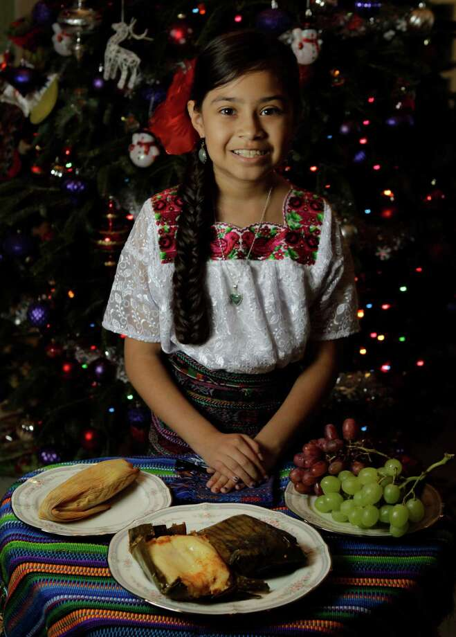 Jaqueline Marroquin, 9,  won the Recipe for Success Foundation writing contest with an essay describing her family's tradition of making Guatemalan tamales, center, at Christmas. Chuchito and grapes also are part of the traditional meal. Photo: Melissa Phillip, Staff / © 2012 Houston Chronicle