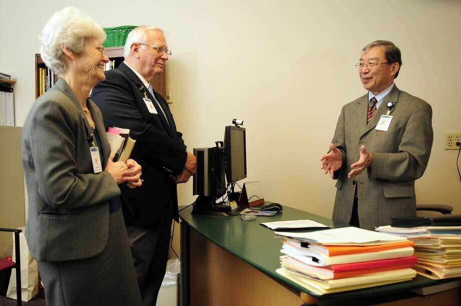 Andy Chao, right, manager of chaplaincy at Memorial Hermann Northeast Hospital in Humble, talks with ministry volunteers Don Wiley, of Humble, and Virginia Hale, of New Caney, about scheduling. Photo: Jerry Baker, Freelance / Greg Krenek