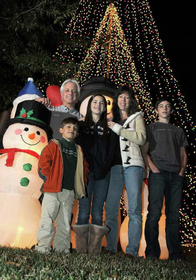 "The Steinhilber family, including Tom, from top left, Kira, 12, a 6th grader at Riverwood Middle School, Patty, and Sean, a Kingwood High School freshman, and Scott, 5, front left, a kindergartner at Shadow Forest Elem. School, show off the Christmas ""tree"" in the front yard of their home in Kingwood. Freelance photo by Jerry Baker Photo: Jerry Baker, Freelance"