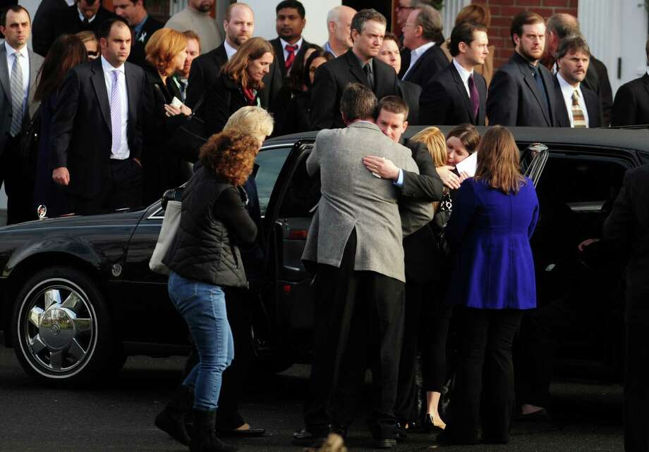Mourners embrace following the funeral for Jessica Rekos, one of 20 children killed in a mass shooting at Sandy Hook Elementary School Friday morning, Tuesday, Dec. 18, 2012 at St. Rose of Lima Roman Catholic Church in Newtown, Conn. Photo: Autumn Driscoll / Connecticut Post