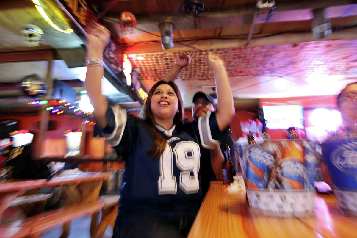 Dallas fans Jay Mendoza (foreground) and Mike Martinez cheer as the Cowboys score a touchdown against the Philadelphia Eagles.