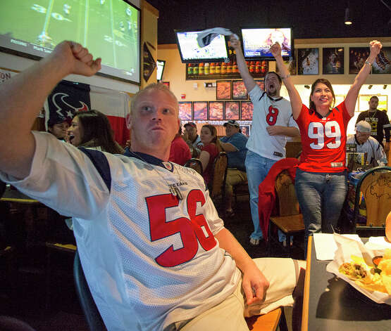 Larry Courtney (from left), David Kemper and Rachel Vasquez of the Houston Texans Fan Club of San Antonio celebrate a touchdown during a Texans game against the Tennessee Titans at Buffalo Wild Wings Grill & Bar at 5860 De Zavala Road on Sunday, Dec. 2, 2012. All three have been fans since day one in 2002. Photo: Michael Miller, For The Express-News / © San Antonio Express-News