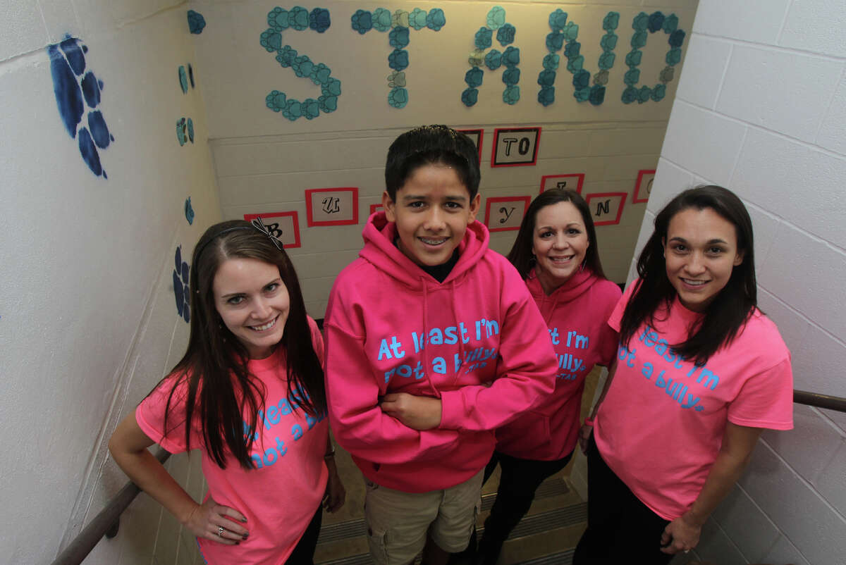 Tejeda Middle School Teachers Kristen Guerra (left), Melissa Hennig (right center) and Marilu Ramey (far right) stand with eighth grade student Steven Jalifi (left center),13, in front of an anti-bullying hallway banner at the school Thursday December 13, 2012. The school's PAWsitiveLeader program has an an anti-bullying message that teaches kids to use smartphones and social media sites responsibly.