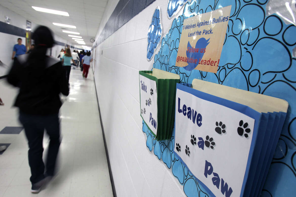 Students at Tejeda Middle School walk past folders on a hall wall that are part of the school's PAWsitiveLeader leader program. Kids can take a