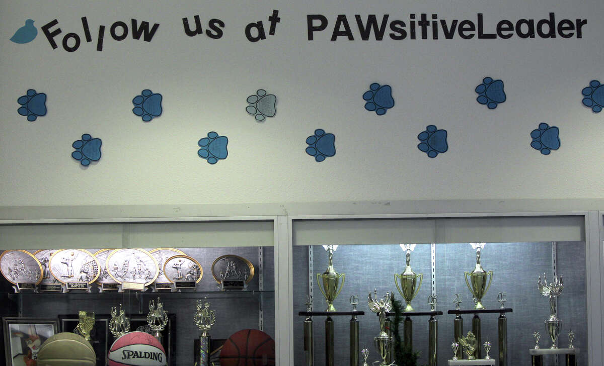 Paws cutouts with positive messages on them are stuck to the hallway walls as a part of Tejeda Middle School's PAWsitiveLeader program. The program teaches students at the school about responsible use of smartphones and social media websites.