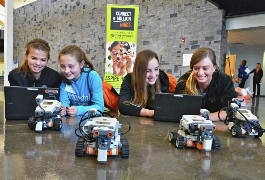 Ballston Spa 7th graders, from left, Maura Smith, Julia Barnum and Kate Wheeler work with SUNY Albany student Theresa LeFebvre, at right, in a Social Robotics workshop during Girl's Inc.'s  5th Annual Girl's Summit at HVCC's TEC-SMART facility in Malta Friday Dec. 14, 2012.  (John Carl D'Annibale / Times Union) Photo: John Carl D'Annibale / 00020479A