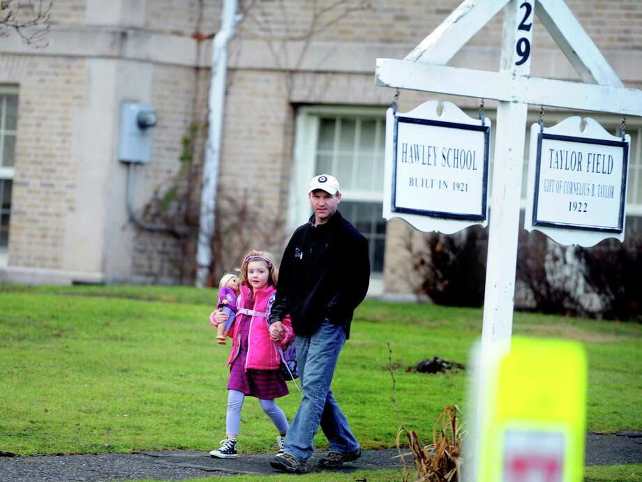 Children leave Hawley School Tuesday, Dec. 18, 2012 following their first day back at school since Friday's mass shooting in Newtown, Conn. Photo: Autumn Driscoll / Connecticut Post