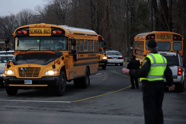 School buses leave Hawley Elementary School, in Newtown, Conn., Dec. 18th, 2012. Tuesday was the first day that students in Newtown went back to class following the mass shooting at Sandy Hook Elementary School last Friday. Photo: Ned Gerard / Connecticut Post