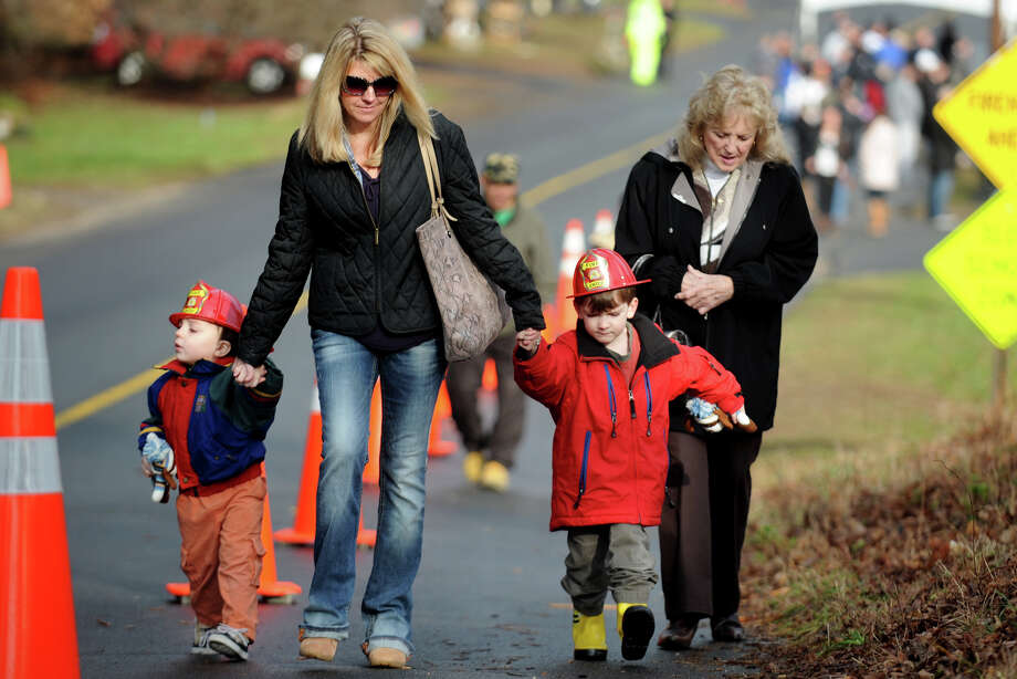 Zachary, 2, and Nathan, 4, Johnston, of Easton, wear the new fire helmets they received from firefighters at Sandy Hook Volunteer Fire Department, in Newtown, Conn. Dec. 18th, 2012. The boys, seen here with their mother, Joelle Johnston, and neighbor Carolette Johnson, visited the Sandy Hook firehouse Tuesday to delivers a gift to first responders. Photo: Ned Gerard / Connecticut Post
