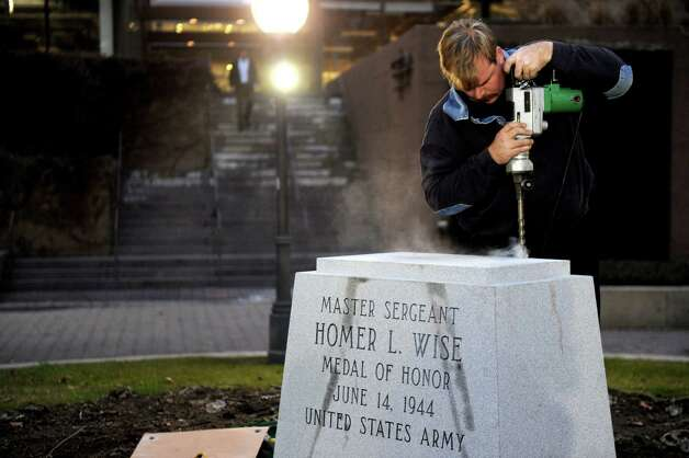 Ned Steinmetz drills holes in the base of a statue of Homer L. Wise in Veterans Park in Stamford on Tuesday, December 18, 2012. Photo: Lindsay Niegelberg, Niegelberg / Stamford Advocate