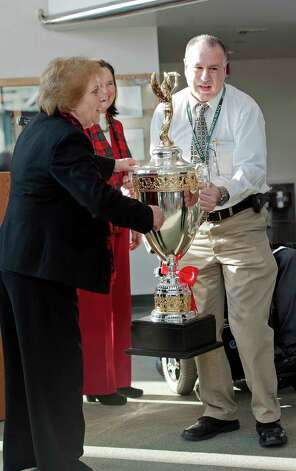 Jim Johnson, security manager for the Government Center takes the Democracy Cup from Lucy Corelli, Stamford CT republican registrar of voters, so he can put it in the display case in the lobby of the Government Center Stamford, CT on Tuesday December 18th, 2012. Photo: Mark Conrad / Stamford Advocate Freelance