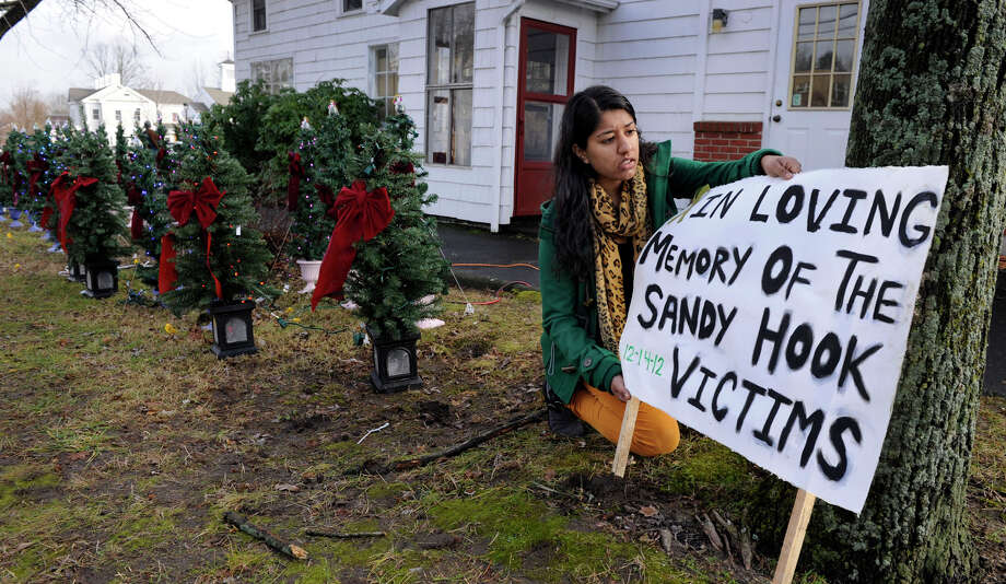 Shelja Patel, 19, whose family owns Newtown Convenience Store, puts up a sign to accompany the 26 Christmas Trees that the family is displaying near their store - one tree for each victim of the Sandy Hook school shooting, Tuesday, dec. 18, 2012. Photo: Carol Kaliff / The News-Times