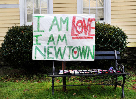 This sign in front of a house on Main Street in Newtown, is one of many memorials in honor of the 26 victims of the Sandy Hook Elementary School shooting last Friday. Photo: Carol Kaliff / The News-Times