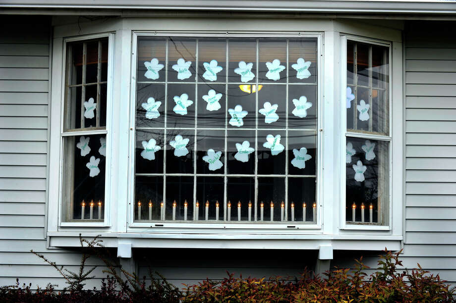 The window at William Pitt Sotheby's International on Church Hill Rd. in Newtown commemorates the victims of the Sandy Hook Elementary School shooting, Tuesday, Dec. 18, 2012. Photo: Carol Kaliff / The News-Times