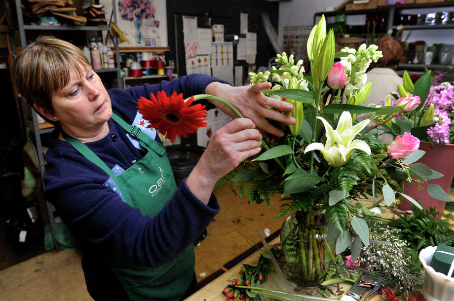 "Valorie Correa, a co-owner of Judd's Flowers in Danbury, works on an arrangement of flowers ordered for one of the memorials for the victims of the Sandy Hook shooting on Friday. Her business has received an abundance of similar orders, some in quanities of 26, one for each of the victims. She says, ""I'll probably be delivering in the middle of the night, just to get through the town."" Photo: Carol Kaliff / The News-Times"